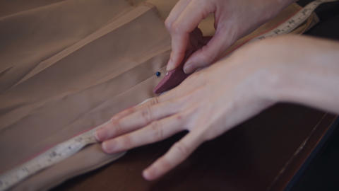 Seamstress making a pattern on beige fabric Footage