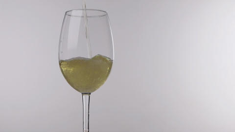 Pouring white wine from bottle into glass on a white background, close up Live Action