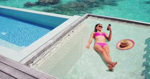 Luxury resort vacation tourist woman relaxing on overwater catamaran net bed Footage