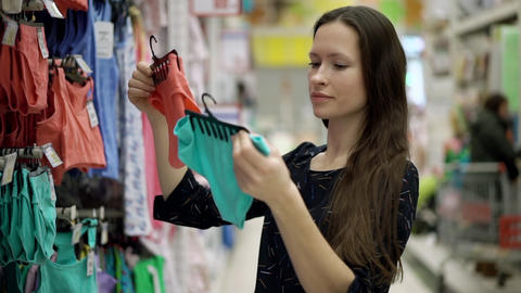 Mother choosing clothes for the baby standing near a shelf of children's clothes Live Action