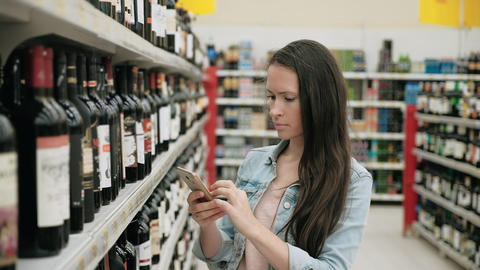 Woman select wine in the supermarket, pretty girl chooses allcohol by smartphone Live Action