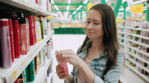 Beautiful woman looking at cosmetics in supermarket. Housewife buying cosmetic Live Action