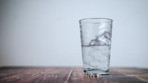 Time lapse shot the ice dissolving in a clear glass on wooden table select focus shallow depth of Footage