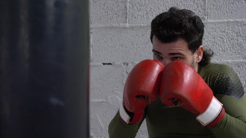 Boxer in boxing gloves kicking combat bag at fight training in fight club Live Action