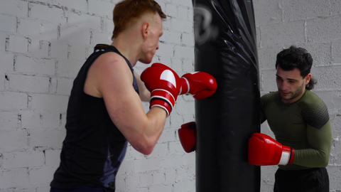 Kickboxer training kick by boxing bag on kickboxing training. Boxerman in gloves Live Action