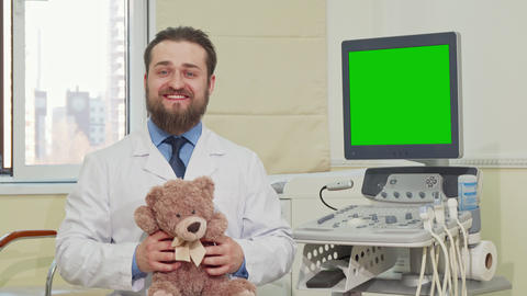 Pediatrician holding teddy bear, ultrasound scanner with green screen on the Live Action