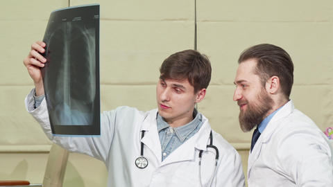 Two male doctors examining lungs x-ray of a patient Live Action