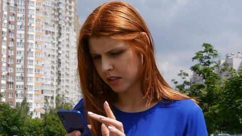 Young beautiful girl with red hair, in the city, can not find information in a Live Action