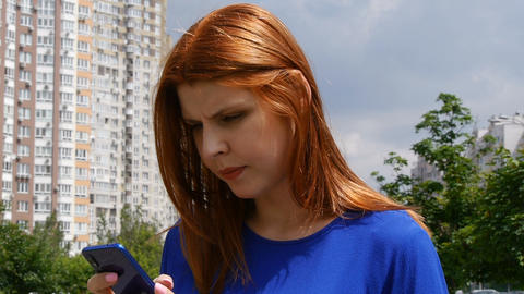 Young beautiful girl with red hair, in the city, found information in the mobile Footage