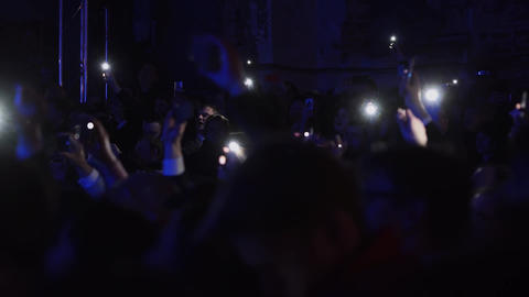 People are dancing holding lighted cellphones in evening at some concert Footage