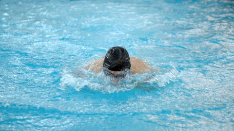 Male swimmer doing butterfly stroke during training in swimming pool, Slow Footage