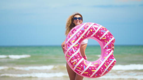 Woman having fun and smile dancing with pink donut. girl in bicini wearing Footage