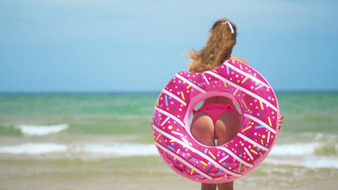 Buttocks girls dancing with pink donut. girl in pink bicini on the beach Footage