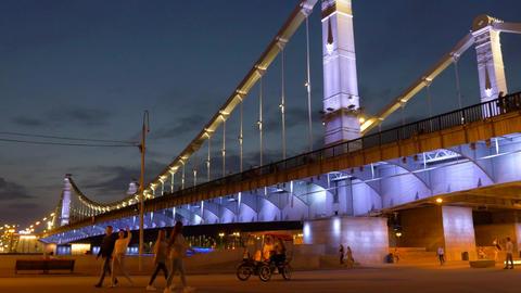 people walk along comfortable embankment at bridge with bright colored lights ビデオ