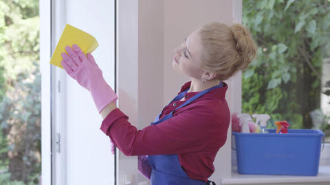 Pretty smiling blond girl in blue apron washing the window with window rag in Footage