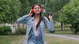 Cheerful girl in headphones walks on the street Footage