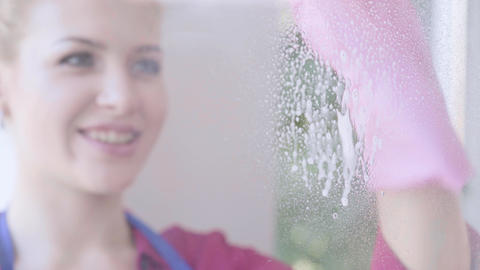 Close-up of pretty smiling blond girl washing the window with window rag in the Footage