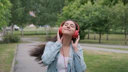 beautiful cheerful girl dancing walking in the park with headphones Footage