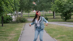 Funny cheerful girl dancing in the park listening to music on headphones. Fun Footage