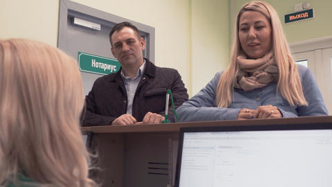 Couple listens to manager behind desk in bank building Footage