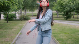 Funny Cheerful girl dancing in the park listening to music on headphones Footage
