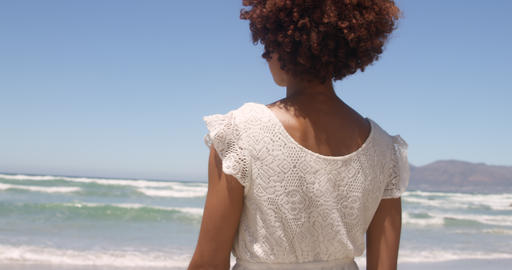 Rear view of young African american woman walking on beach in the sunshine 4k Live Action