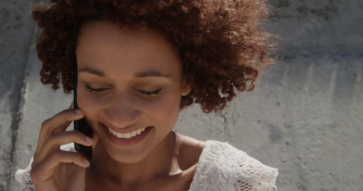 Front view of young African american woman talking on mobile phone at beach in the sunshine 4k Live Action