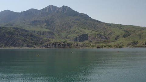 Panoramic aerial view. Kayak swimming along coastal strip on majestic mountain landscape. Calm blue Footage