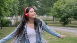 Stylish cheerful girl dancing in the park listening to music on headphones Footage