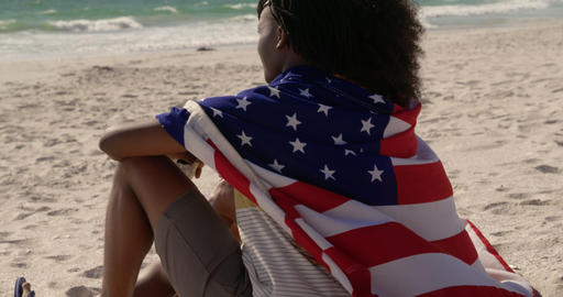 Side view of African american couple wrapped in American flag sitting together on the beach 4k Live Action