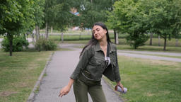 Cheerful hipster girl with long hair in a good mood is dancing in the park to Footage