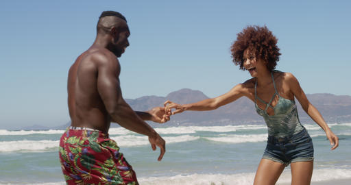 Couple dancing together on beach in the sunshine 4k Live Action