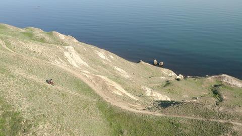 Panorama aerial view. Dirt mountain road runs along hillside along sea. Man rides mountain bike in Live Action