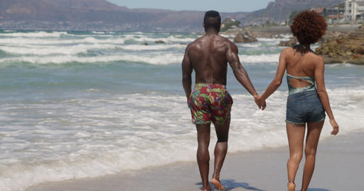 Couple walking together on beach in the sunshine 4k Live Action