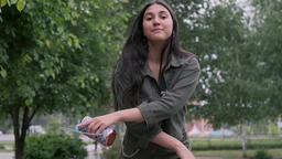 Cheerful hipster brunette girl dancing in a park to the music holding a portable Footage