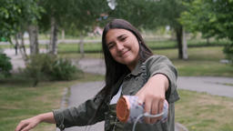 Cheerful hipster girl goes and dances in the park to the music while holding a Footage