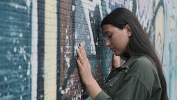 Beautiful hipster girl posing near the wall with graffiti. Hands on the wall Footage