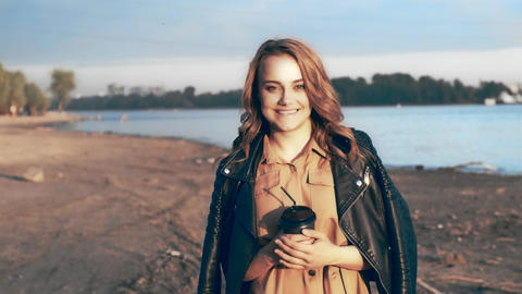 Pretty girl in a black jacket walking near the river and drinking coffee Footage