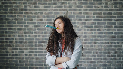 Portrait of unhappy young woman blowing party horn with sad face near brick wall Footage