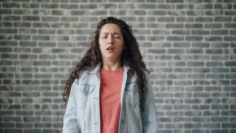 Portrait of ill young woman sneezing looking at camera on brick wall background Footage