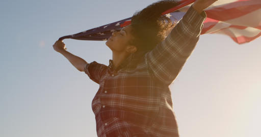 Woman waving american flag on the beach in the sunshine 4k Live Action