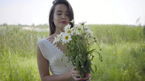 Portrait glamorous young girl with brunette hair wearing a long white summer Footage