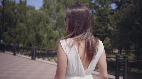 Portrait glamorous young girl wearing sunglasses and a long white summer fashion Footage