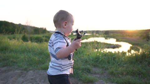 A small boy holds a small horse toy, happily runs with it on the road at sunset Footage