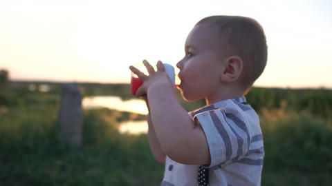 A boy drinks a drink from a baby bottle being in nature at sunset, slow motion Footage