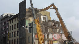 High Reach Demolition Excavator Breaking Down Upper Story of Old Apartment Building Live Action