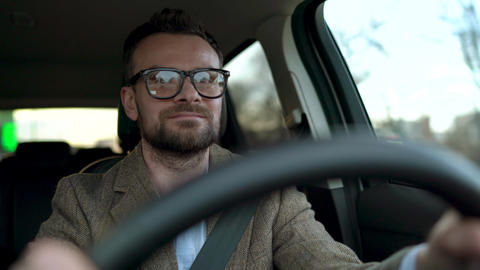 Satisfied bearded man in glasses driving a car down the street in sunny weather Live Action