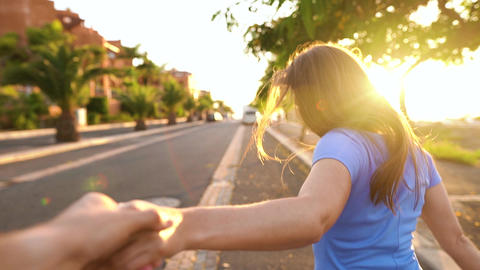 Follow me - happy young woman pulling guy's hand - hand in hand running on a Live Action