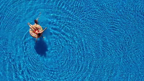 Aerial view of couple having fun in the pool, man is swimming and a woman is Footage