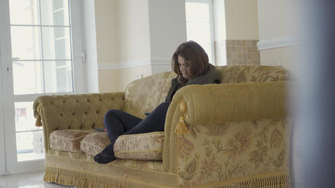 Young beautiful girl sitting and relaxing with tablet on sofa in cozy living Footage